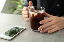 Woman With Glass Cup Of Cold Coffee And Mobile Phone At Grey Table