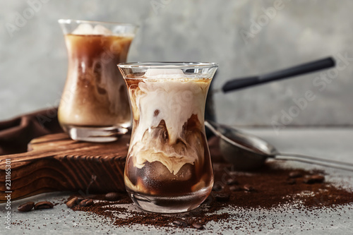 Fotografía  Glass with cold coffee on grey table