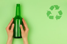 Green Recycle Symbol Sign Symbolizes Refuse Reuse Recycle Concept And Glass Of Bottle In Hand In Green Isolated Background. Ecology Recycle, Environment Issue, Safe Planet Concept