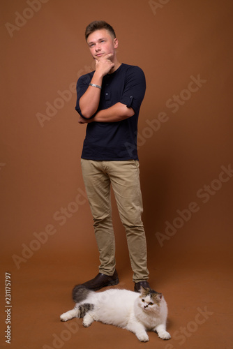 Foto  Studio shot of young handsome man against brown background