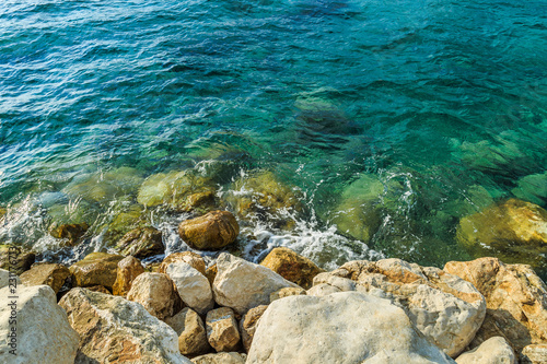Fotografia  Sea water and pebbles on a sunny summer day