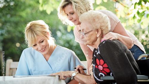 Fotografía Seniorin beim Kreuzworträtzeln mit Tochter und Pflegerin