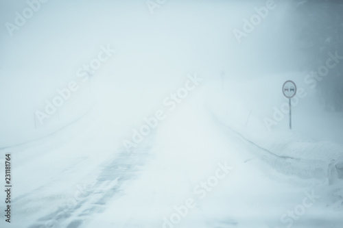 Printed kitchen splashbacks Light blue snow and fog on the winter road landscape / view of the seasonal weather a dangerous road, a winter lonely landscape