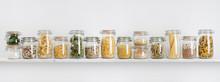 Assortment Of Uncooked Groceries In Glass Jars Arranged On Shelf