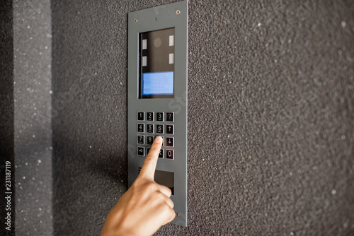 Valokuva  Close-up of intercome keyboard of residential building with finger entering code