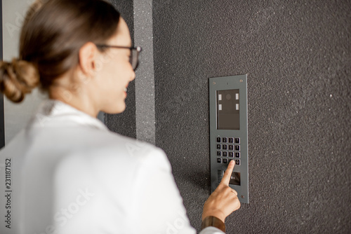 Valokuva  Young business woman in white suit entering code on the intercom keyboard of the