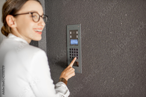 Fényképezés  Young business woman in white suit entering code on the intercom keyboard of the