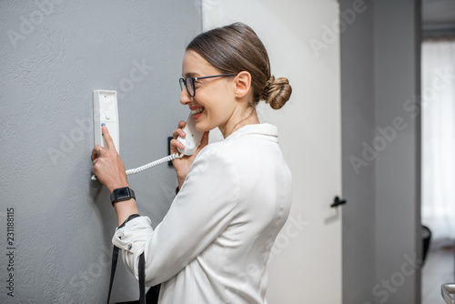 Fototapeta  Woman opening the door from the intercom phone standing in the apartment