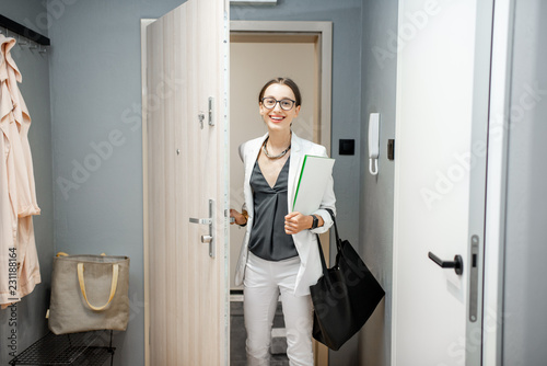 Fototapeta Young business woman entering the apartment returning from the work to home obraz