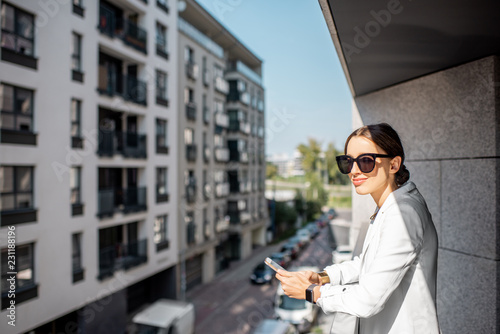 Young business woman in white suit and sunglasses on the balcony of the apartmen Tapéta, Fotótapéta