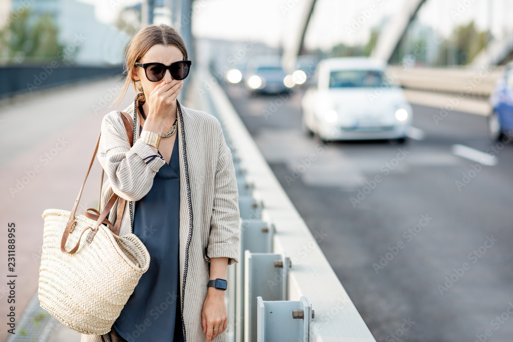 Fototapeta Woman closing her nose feeling bad because of the air pollution on the bridge with traffic in the city