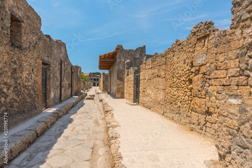 Fotografia  An ancient cobbled street in the ruins of Pompeii, Italy.