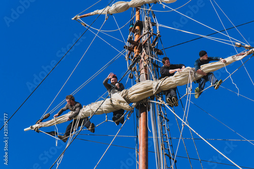Leinwand Poster Sailors work with sails at a height on a traditional sailboat