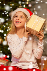 Fototapeta christmas, holidays and childhood concept - smiling girl in santa helper hat with gift box at home