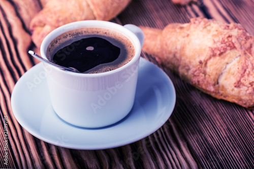 Fotografie, Obraz  Cup of coffee with croissants on a wooden table