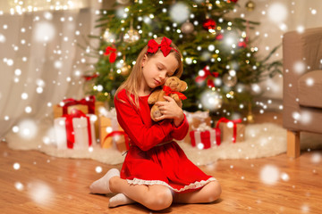 Fototapeta christmas, holidays and childhood concept - girl in red dress hugging teddy bear at home