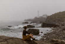 Woman Walking Along A Foggy Coast With Lighthouse