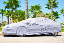 Hot Countries, Protection From Heating The Car. Parked Car Covered With A Cover From The Sun's Rays. The Car Is In The Parking Lot Surrounded By Palm Trees.