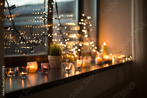 Fotografia  hygge, decoration and christmas concept - candles burning in lanterns on window