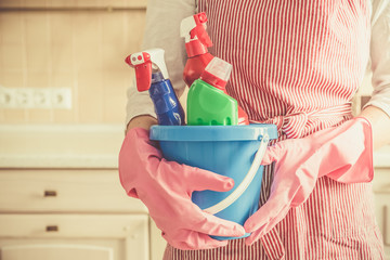 Fototapeta Cleaning concept - female holding cleaning supplies in blue basket, copy space, kitchen background