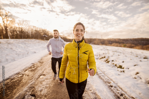 Poster Glisse hiver Young Caucasian couple running together in nature in winter. Couple wearing winter sportswear and having headphones in ears.