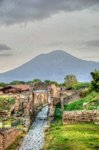 Fotografie, Obraz The ruins of the ancient Pompeii with the Vesuvius volcano in the back