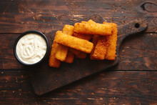 Pile Of Golden Fried Fish Fingers With White Garlic Sauce Placed On Chopping Board On Dark Wooden Background.