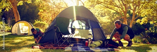 Obraz Boy setting up the tent at campsite - fototapety do salonu