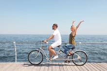 Couple Riding Tandem Bike Near Sea On Sunny Day
