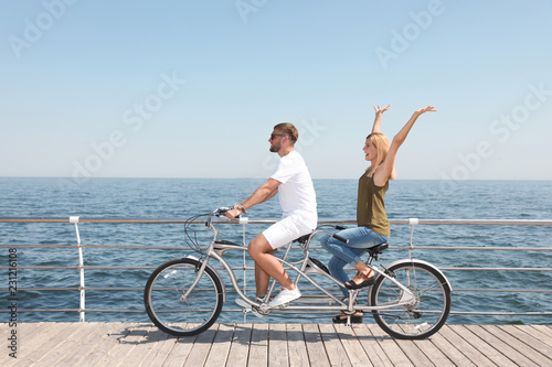 Couple riding tandem bike near sea on sunny day
