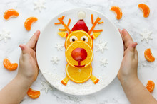 Child Holding Plate With Edible Fruit Reindeer, Christmas Food Art