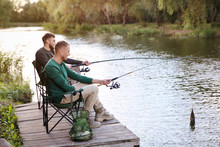 Friends Fishing On Wooden Pier At Riverside. Recreational Activity