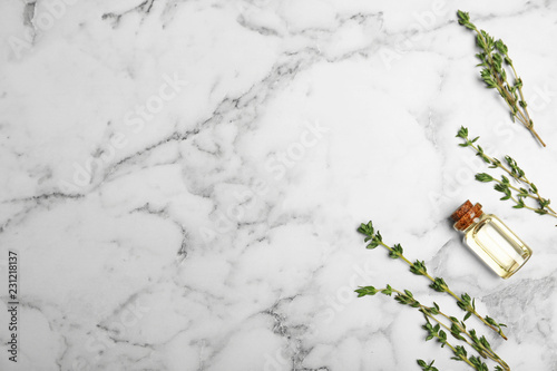Essential oil in glass bottle, thyme and space for text on marble background, flat lay