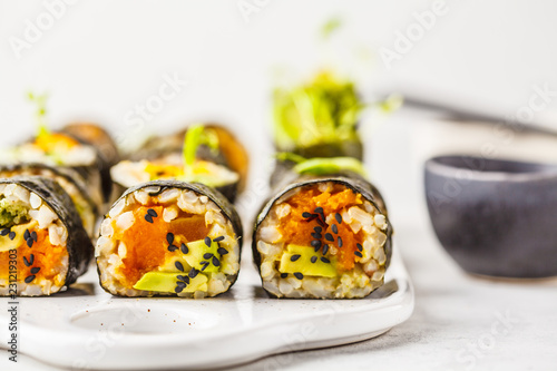 Vegan sushi rolls with pumpkin, brown rice and avocado.