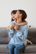 Beautiful Laughing Mother And Preschool Daughter Sitting On Couch Embracing, Vertical View. Happy Smiling Mom Enjoy Free Time With Pretty Child In Living Room At Home Have Good Friendly Relationships