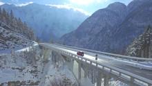 AERIAL Red Car Crosses The Concrete Bridge Build In The Idyllic Snowy Wilderness