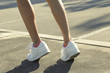 female legs in sneakers close up running down the road in the morning