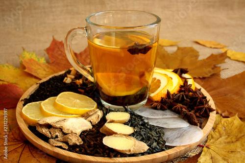 Fototapeta Rozgrzewająca jesienna herbata, różne rodzaje herbaty i przyprawy na tacy, obok jesienne liście obraz