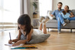 canvas print picture - Diverse family in living room at home. Focus on little preschool adorable concentrated daughter lying at soft cushion on warm wooden floor young parents married couple sitting on sofa looking at kid