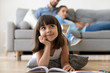 Leinwandbild Motiv Close up little adorable thoughtful smiling daughter dreaming lying at cushion on warm floor with book in living room at modern home, resting married couple parents on background, focus on small kid
