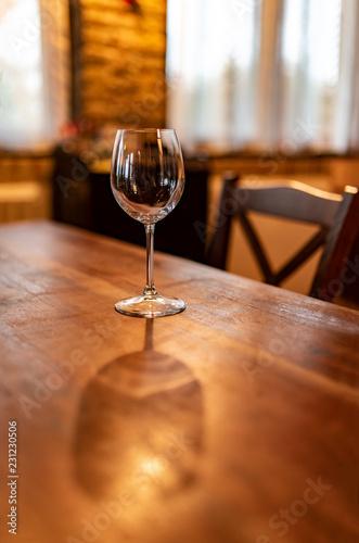 Bicchiere di vetro in una cantina, pronto per essere riempito di vino e per la degustazione, in luci morbide