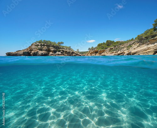 Rocky coast with an islet and sand underwater, split view half above and below water surface, Mediterranean sea, Catalonia, l'Illot, L'Ametlla de Mar, Tarragona, Costa Dorada, Spain