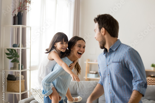 Young happy mother laughing carrying on back piggybacking little daughter catching dad playing with diverse family having fun together Canvas Print