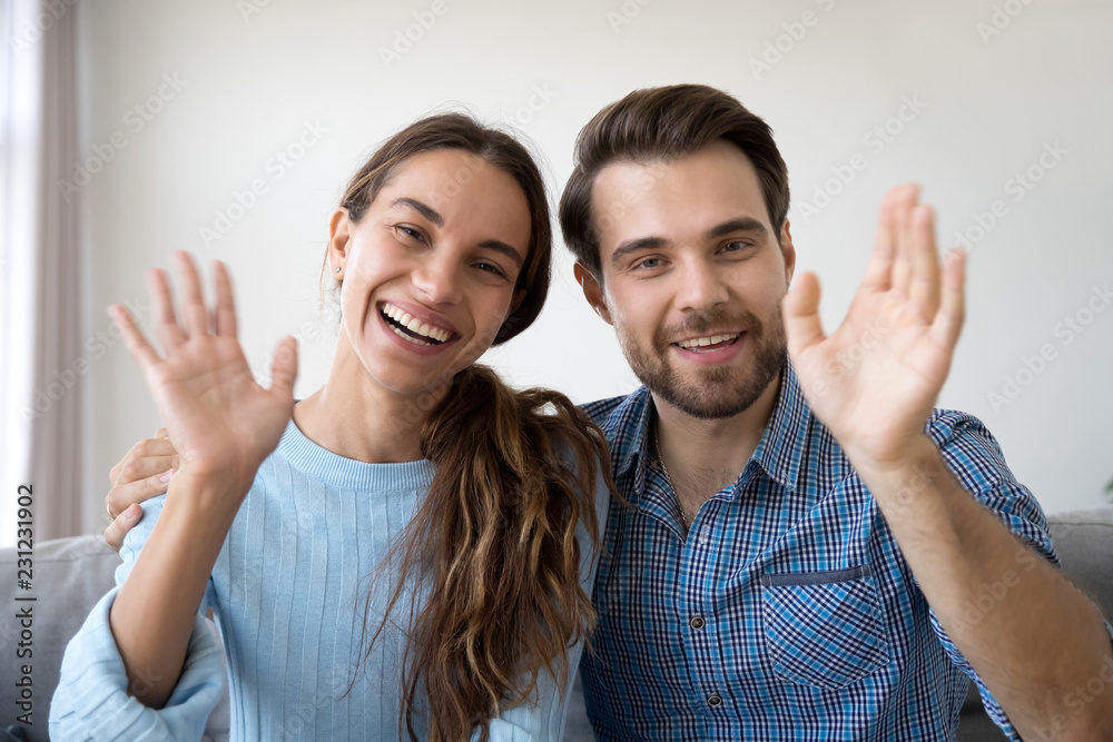 Fototapety, obrazy: Head shot married couple sitting on sofa at home. Portrait wife and husband waving hands looking at camera smiling saying hello greeting or goodbye. First acquaintance or online communication concept