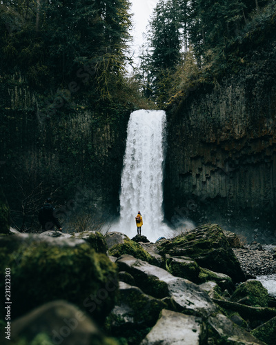 Rear view of woman looking at waterfall in forest - 231232303