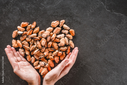 Hands holding frozen peeled mussels in shape of heart over slate stone background. Seafood, top view, flat lay, copy space