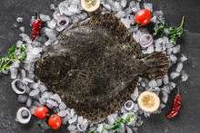 Raw Whole Flounder Fish With Spices On Ice Over Dark Stone Background. Creative Layout Made Of Fish, Top View
