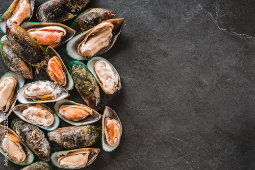 Raw kiwi mussels on slate stone background. Seafood, Shellfish, top view, flat lay, copy space