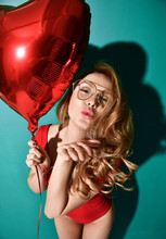 Beautiful Curly Hair Young Woman In Clear Aviator Glasses Hold Big Red Star Balloon Blow Kiss Sign With Lips On Mint Background