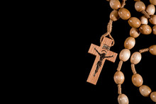 A Brown Rosary Lying On A Blac...
